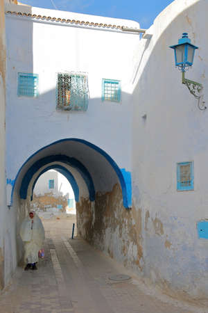 KAIROUAN, TUNISIA - DECEMBER 12, 2019: Typical cobbled and narrow street  inside the historical medina of Kairouan, with blue and white colors, an arcade and a woman traditionally dressed in white