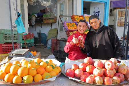 KAIROUAN, TUNISIA - DECEMBER 13, 2019: Portrait of two welcoming market sellers in a local fruit and vegetable market next to the medina