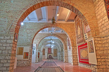 KAIROUAN, TUNISIA - DECEMBER 13, 2019: The colorful interior of the ONAT Museum, with an exhibition of colorful carpets within a traditional architecture