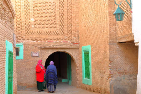NEFTA, TUNISIA - DECEMBER 14, 2019: The historical brick decorated medina of Nefta, with women dressed with colorful clothes