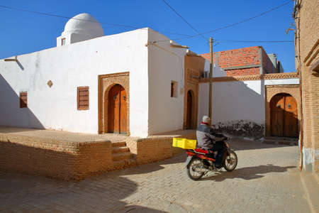 NEFTA, TUNISIA - DECEMBER 15, 2019: Typical cobbled and narrow street  inside the brick decorated medina of Nefta, with traditional wooden doors and the mosque Sidi M Barek Editorial