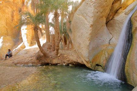 CHEBIKA, TUNISIA - DECEMBER 16, 2019: The oasis of Chebika near Nefta, with a waterfall, palm trees and mineral rocks Standard-Bild - 141072922