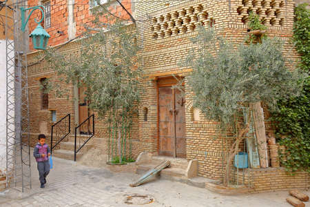 NEFTA, TUNISIA - DECEMBER 17, 2019: Typical cobbled and narrow street  inside the brick decorated medina of Nefta, with traditional wooden doors Standard-Bild - 141072924