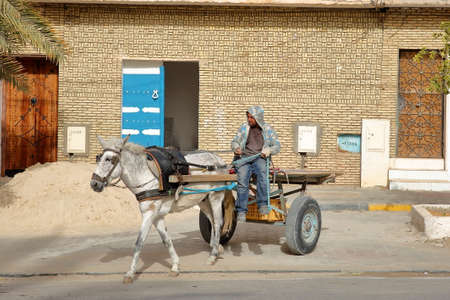 NEFTA, TUNISIA - DECEMBER 18, 2019: A traditional carriage pulled by a horse in the main street of Nefta, with patterns of brick and colorful doors in the background
