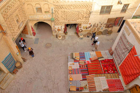 TOZEUR, TUNISIA - DECEMBER 18, 2019: The historical medina of Tozeur (Ouled el Hadef), decorated with patterns of bricks, arcades and a display of colorful carpets Editorial