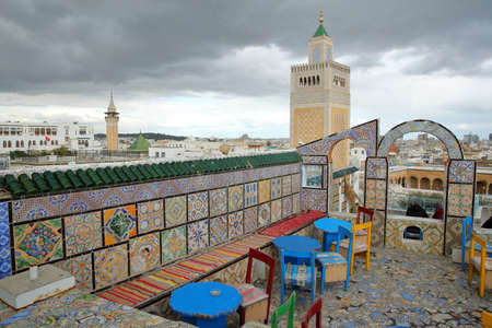 TUNIS, TUNISIA - DECEMBER 29 2019: Colorful tiled terrace overlooking the medina, with a view on the minaret of Ez Zitouna Mosque (Great Mosque) and the minaret of Hammouda Pacha Mosque