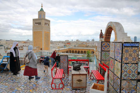 TUNIS, TUNISIA - DECEMBER 29 2019: Colorful tiled terrace overlooking the medina, with a view on the minaret of Ez Zitouna Mosque (Great Mosque) and a local family traditionally dressed