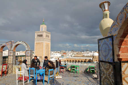 TUNIS, TUNISIA - DECEMBER 29 2019: Colorful tiled terrace overlooking the medina, with a view on the minaret of Ez Zitouna Mosque (Great Mosque)