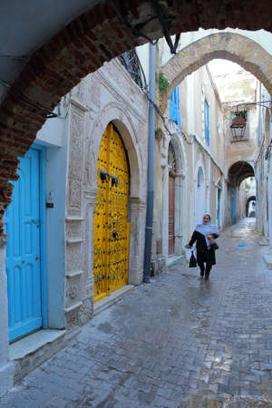 TUNIS, TUNISIA - DECEMBER 30 2019: Typical cobbled and narrow street with colorful doors and arcades inside the historical medina of Tunis, and with a local woman traditionally dressed