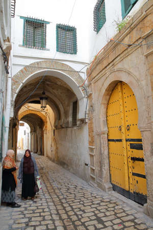 TUNIS, TUNISIA - DECEMBER 30 2019: Typical cobbled and narrow street with arcades inside the historical medina of Tunis, and with two local women traditionally dressed Editorial