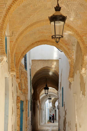 TUNIS, TUNISIA - DECEMBER 30 2019: Typical cobbled and narrow street with colorful doors, columns and arcades inside the historical medina of Tunis
