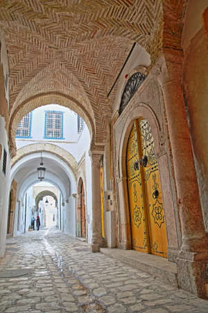 TUNIS, TUNISIA - DECEMBER 30 2019: Typical cobbled and narrow street with colorful doors, columns and arcades inside the historical medina of Tunis Standard-Bild - 141073431