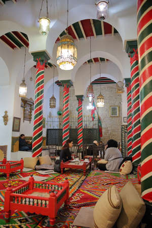TUNIS, TUNISIA - DECEMBER 30 2019: The impressive colorful interior of El Mrabet Cafe, located inside the medina, with twisted columns, a high vaulted ceiling and a focus on local women having a coffee