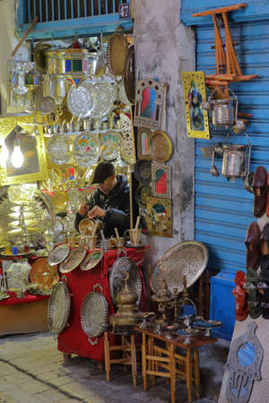 TUNIS, TUNISIA - DECEMBER 31, 2019: Brass and copper craftsman at work in the souk inside the medina