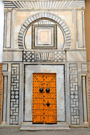 TUNIS, TUNISIA - DECEMBER 31, 2019: The impressive entrance to Dar Othman Palace, located inside the medina, with an ornate wooden door and carved walls with columns.