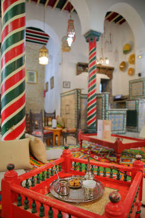 TUNIS, TUNISIA - JANUARY 01, 2020: The impressive colorful interior of El Mrabet Cafe, located inside the medina, with twisted columns, a high vaulted ceiling and a focus on a turkish coffee cup with a copper tray