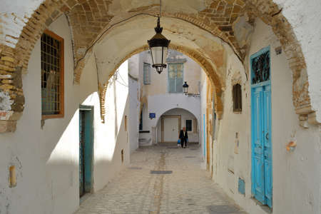 TUNIS, TUNISIA - JANUARY 02, 2020: Typical cobbled and narrow street (Dey street) with colorful doors and arcades inside the historical medina of Tunis