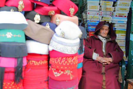 TUNIS, TUNISIA - JANUARY 02, 2020: A chechia shop (traditional hats) located in the souk inside the medina, with a focus on a seller traditionally dressed Standard-Bild - 141073452
