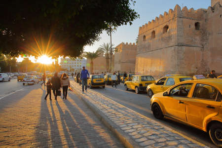 SFAX, TUNISIA - DECEMBER 22, 2019: The impressive ramparts of the medina with a taxi stand at sunset (sun star)