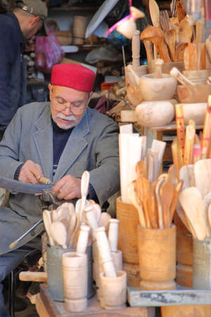 SFAX, TUNISIA - DECEMBER 24, 2019: A craftsman at work in the souk inside the medina. He is wearing a chechia (traditional hat) Standard-Bild - 141073467