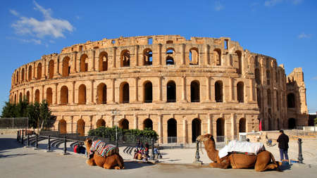 EL JEM, TUNISIA - DECEMBER 24, 2019: The impressive Roman amphitheater of El Jem, with camels in the foreground