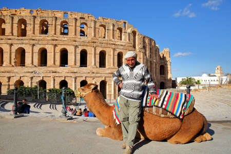EL JEM, TUNISIA - DECEMBER 24, 2019: A local tunisian posing with his camel in front of the impressive Roman amphitheater of El Jem