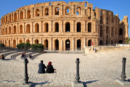 EL JEM, TUNISIA - DECEMBER 24, 2019: The impressive Roman amphitheater of El Jem, with a tunisian couple in the foreground Standard-Bild - 141073471