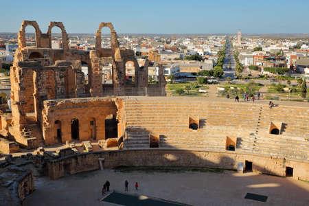 EL JEM, TUNISIA - DECEMBER 24, 2019: The impressive Roman amphitheater of El Jem, with the city of El Jem in the background Standard-Bild - 141073472
