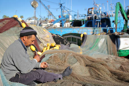 MAHDIA, TUNISIA - DECEMBER 26, 2019: A fisherman repairing his net at the fishing port, with colorful nets around him and trawlers in the background Editorial