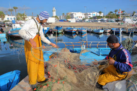 MAHDIA, TUNISIA - DECEMBER 27, 2019: Fishermen repairing their net at the fishing port, with the city of Mahdia in the background