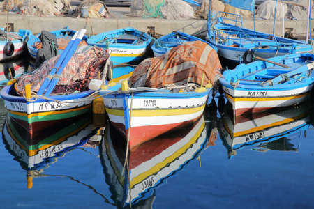 MAHDIA, TUNISIA - DECEMBER 27, 2019: Colorful fishing boats and reflections at the fishing port Editorial