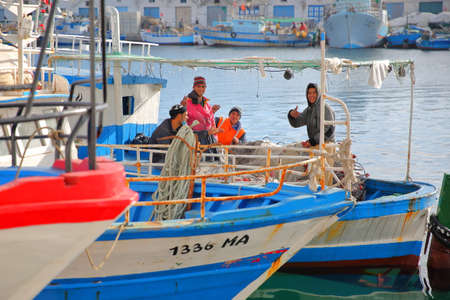 MAHDIA, TUNISIA - DECEMBER 27, 2019: Fishermen on their fishing boat smiling at the camera at the fishing port