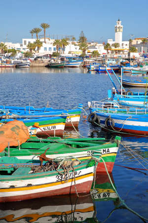 MAHDIA, TUNISIA - DECEMBER 27, 2019: The fishing port with colorful fishing boats and the city of Mahdia in the background