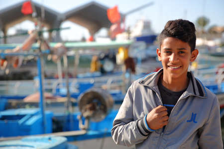 MAHDIA, TUNISIA - DECEMBER 27, 2019: Portrait of a smiling teenager at the fishing port, with fishing boats in a blurred background Standard-Bild - 141073483