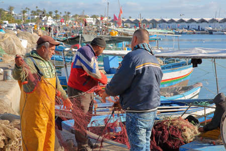 MAHDIA, TUNISIA - DECEMBER 27, 2019: Fishermen repairing their net at the fishing port, with colorful fishing boats in the background