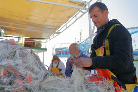 MAHDIA, TUNISIA - DECEMBER 27, 2019: Portrait of a fisherman repairing his net on his boat at the fishing port, with colorful fishing nets around him Editorial