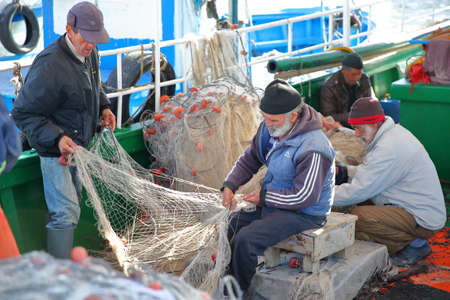 MAHDIA, TUNISIA - DECEMBER 27, 2019: Fishermen repairing their net on their boat at the fishing port, with colorful fishing nets around them