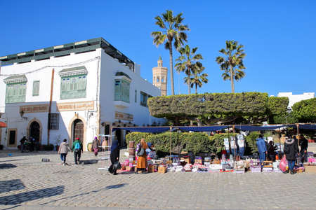 MAHDIA, TUNISIA - DECEMBER 27, 2019: The Friday souk in the medina, with whitewashed traditional houses and the minaret of Soliman Hamza mosque in the background