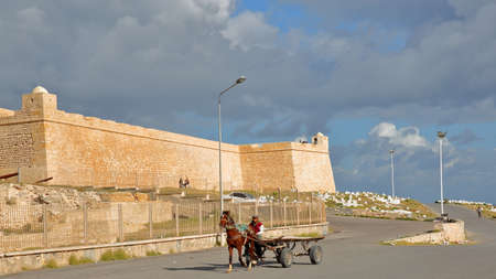 MAHDIA, TUNISIA - DECEMBER 28, 2019: A carriage pulled by a horse in front of the Ottoman fortress Borj el Kebir Editorial