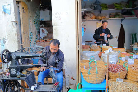 SFAX, TUNISIA - DECEMBER 25, 2019: A cobbler at work inside the medina with a sewing machine and stalls of nuts on the right side Editorial