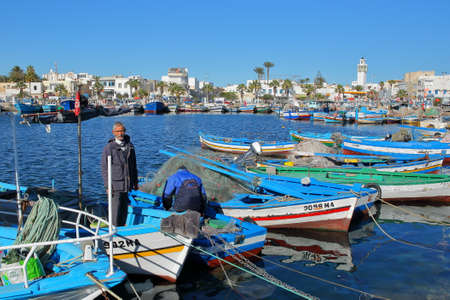 MAHDIA, TUNISIA - DECEMBER 26, 2019: The fishing port with colorful fishing boats and the city of Mahdia in the background. A fisherman posing for the camera