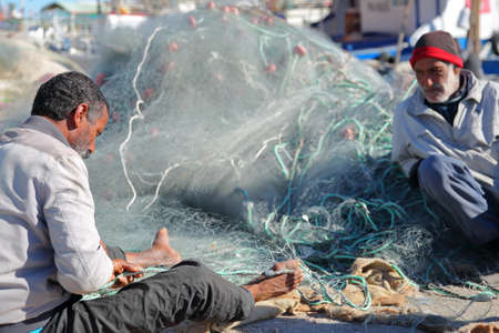 MAHDIA, TUNISIA - DECEMBER 26, 2019: A fisherman repairing his net at the fishing port