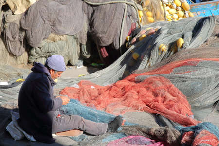 MAHDIA, TUNISIA - DECEMBER 26, 2019: A fisherman repairing his net at the fishing port, with colorful nets around him