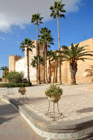 The impressive ramparts of the medina surrounded by colorful palmtrees and a large cobbled walkway in Sfax, Tunisia Standard-Bild