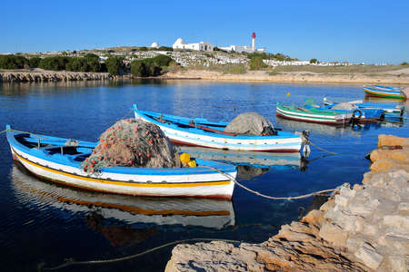 The old Fatimid port of Mahdia, Tunisia, with colorful fishing boats and the mosque lighthouse in the background Standard-Bild