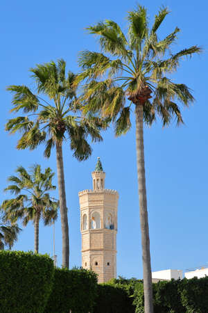 Close-up on the minaret of Soliman Hamza mosque surrounded by palm trees in the city of Mahdia, Tunisia