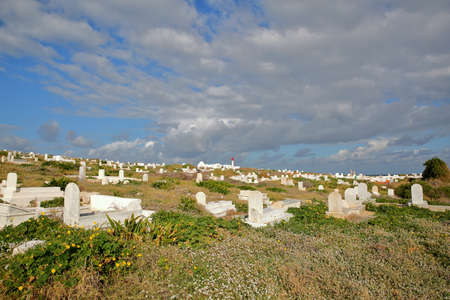 View of hundreds of whitewashed tombs, located at the top end of the peninsula in Mahdia, Tunisia, with the mosque lighthouse in the background Standard-Bild