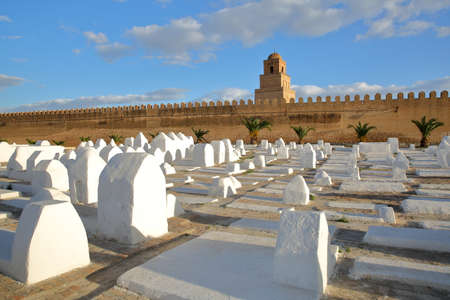 The Great Mosque of Kairouan, Tunisia, viewed from outside the ramparts and with whitewashed tombs in the foreground