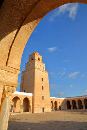The courtyard of the Great Mosque of Kairouan, Tunisia, with the minaret viewed from an arcade Standard-Bild - 141775093