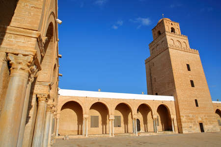 The courtyard of the Great Mosque of Kairouan, Tunisia, with columns and the minaret Standard-Bild - 141775098